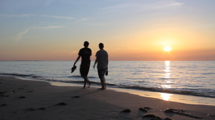 silhouettes of two young boy friends walking at beach at sunset