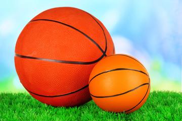 Basket balls, on green grass, on bright background