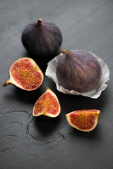 Whole and sliced figs on black wooden background, vertical shot
