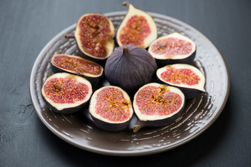 Ceramic plate with sliced ripe fig fruits, horizontal shot