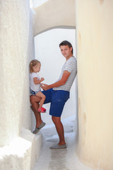 Young father with her litttle daughter in old greek village on