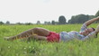 Beautiful young brunette woman lying on the meadow, slow motion