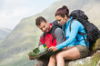 Couple resting after hiking uphill and reading map