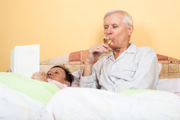 Senior enjoying glass of alcohol in bed