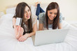Smiling friends using a laptop to shop online lying on bed