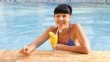 beautiful woman relaxing in swimming pool with cocktails