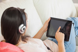Girl using her tablet pc on the sofa and listening to music