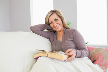 Smiling woman holding a book and lying on a sofa