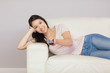 Cheerful asian girl lying on the couch watching tv