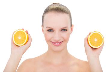 Joyful pretty blonde model showing two orange halves