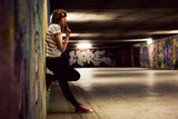 Stylish girl standing in grunge graffiti tunnel, shanty town