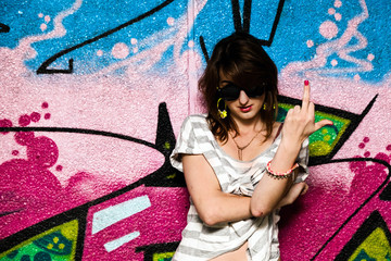 Stylish girl showing fuck off against graffiti wall