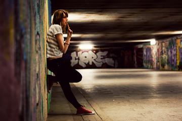 Stylish girl standing in grunge graffiti tunnel, shanty town