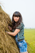 Portrait of pretty brunette standing near the haystack