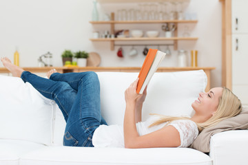 junge frau liegt auf dem sofa und liest ein buch