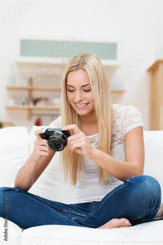 junge frau sitzt auf dem sofa und schaut auf ihre digitalkamera