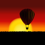 Sunset landscape with air balloon silhouette.