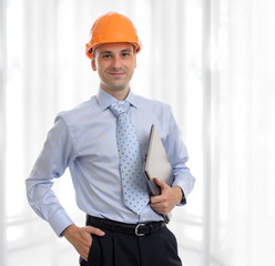 Young male architect wearing helmet and holding laptop