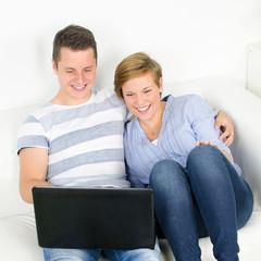 glückliches paar schaut auf notebook