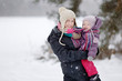 Young mother and her daughter at winter day