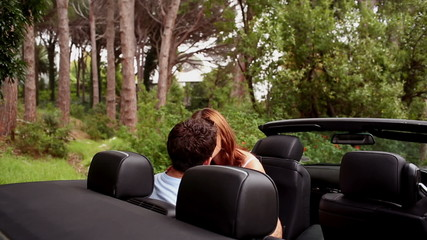Romantic couple kissing in a convertible car