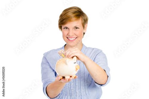 frau steckt geld ins sparschwein