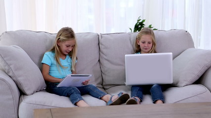 Sisters using laptop and tablet pc