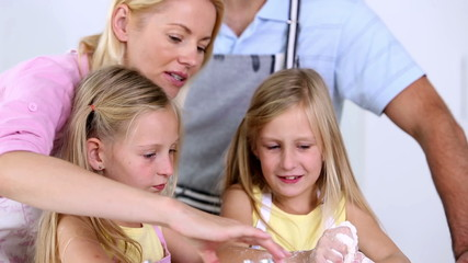 Twin sisters making pastry with their parents