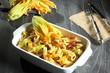 pasta con fiori di zucchino  e pancetta sfondo grigio
