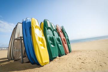 plastic recreational canoes on a sandy british beach