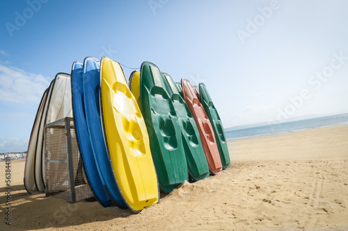 plastic recreational canoes on a sandy british beach