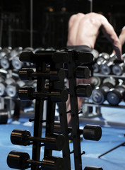 A set up with many dumbbells and a man