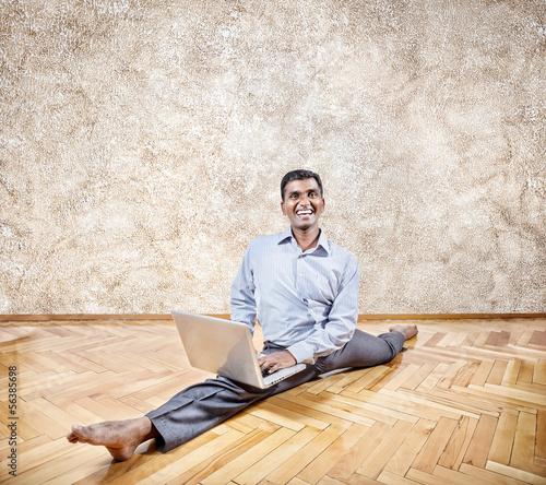 Indian man doing yoga with laptop