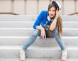 Stylish girl sitting on steps