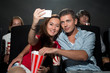 Couple watching movie at cinema and photographing themselves