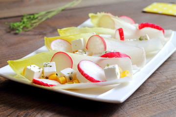 Endives or chicory salad with feta cheese, radishes and corn