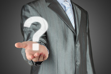 Businessman with question mark on dark background.