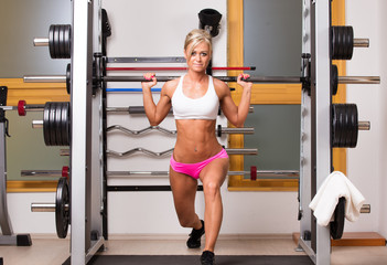 Woman lifts dumbbells in sport centre to develop muscles