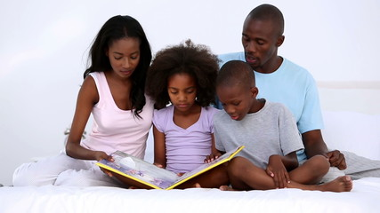 Family reading book on bed