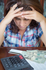 Hispanic woman counting money at home to pay the bills