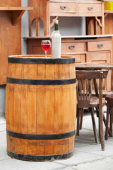 wooden barrel with bottles of wine and glass, chair and table in