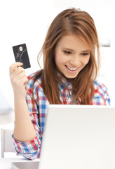 happy teenage girl with laptop and credit card