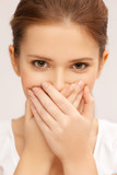 face of beautiful teenage girl covering her mouth