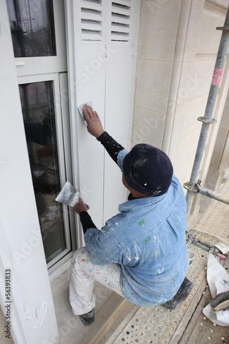 Man sanding wooden shutter