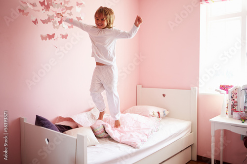 Young Girl Jumping On Her Bed