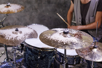 Drummer sits at drumset, cymbals and drums powdered with snow