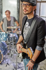 Guitarist and drummer in studio, focus on guitarist face