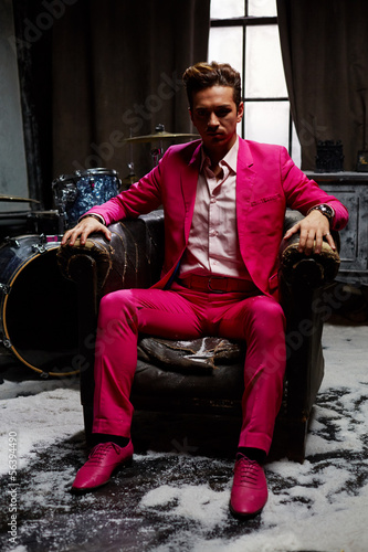 Young man in pink suit sits in semidarkness in old armchair