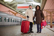 Young man and young woman stand with big red roll-on bag