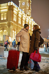 Young man and young woman stand on railway platform in winter